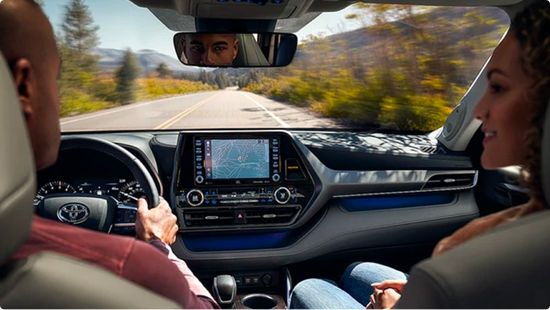 Drivers using Toyota's Audio Multimedia and Connected Services system on the dashboard inside their used Toyota